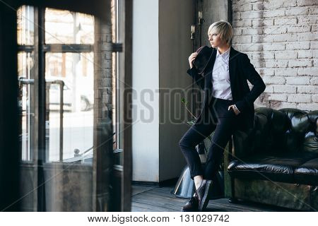 Beautiful stylish girl standing in a cafe and waiting for someone