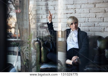 Blonde girl sitting on the couch and pointing at something in a cafe, street reflection in window