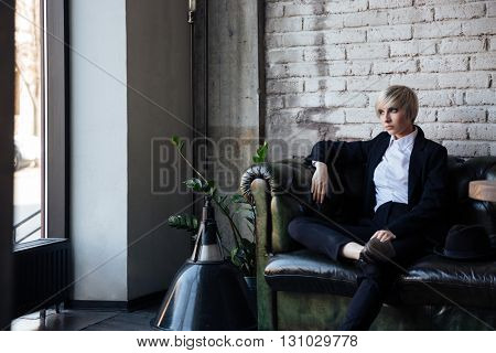 Seriously lookind blonde girl sitting in a cafe and thinking about something