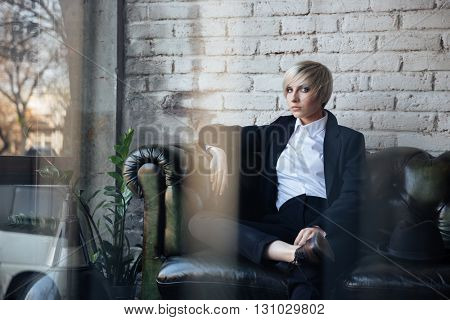 Blonde girl sitting on the couch and looking seriously in the cafe, street reflection in window