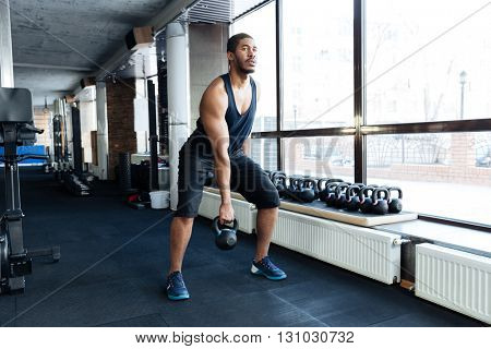 Fit healthy man exercising with kettlebell in the gym