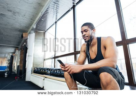 Fitness healthy man with headphones using smartphone in the gym after workout