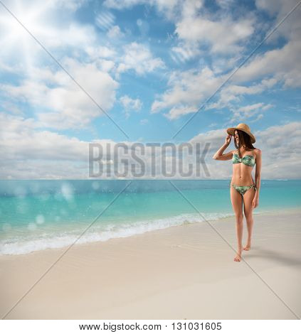 Girl with straw hat walking on beach