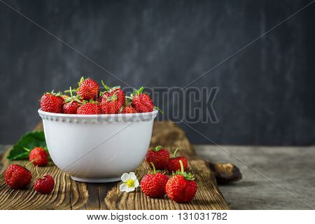 Red juicy strawberries in white bowl on dark wooden background. Selective focus.