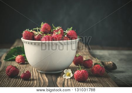 Red juicy strawberries in white bowl on dark wooden background. Vintage toning. Selective focus.