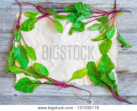 Colorful frame made of fresh tiny beets on shabby craft paper with copy space for your design. Top view. Wooden background.