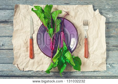 Two fresh beetroots on purple plate with battered craft paper as a background. Served with fork and knife. Selective focus toned.