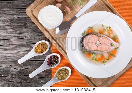 red fish soup with vegetables and dill in a white wide rim dish on a cutting board on a table mat on an old rustic tableview from above