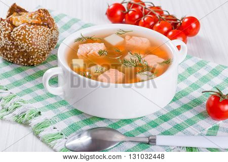 Salmon soup with carrot and potato seasoned with dill in white bowl on the checkered table napkin accompanied with cheese bread roll and cherry tomatoes