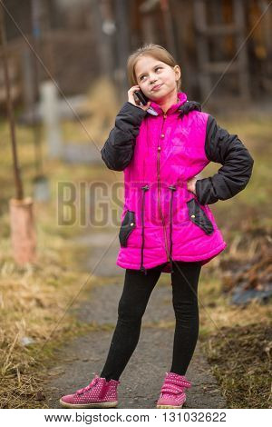 Ten-year girl talking on the phone standing on the street.