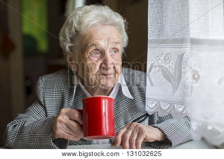 An elderly woman with a Cup of coffee at the table near the window.