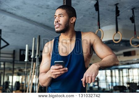 Pensive sports man holding smartphone while resting in the gym