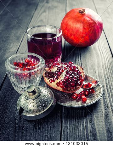 Pomegranate slices grains and juice on rustic wooden table. Toned. Selective focus.