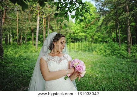 Portrait Of Cute Bride With Peony Wedding Bouquet At Hands At Wood