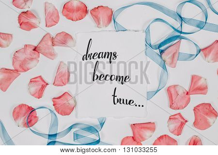 quote Dreams become true written in calligraphy style on paper with pink petals and blue ribbon. Flat lay, top view.