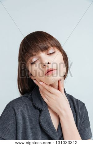 Beauty portrait of a young relaxed woman with closed eyes standing isolated on a white background