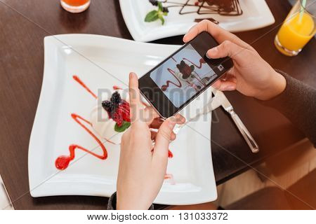 Top view of young woman hands taking pictures of sweet tasty dessert on white square plate using smartphone