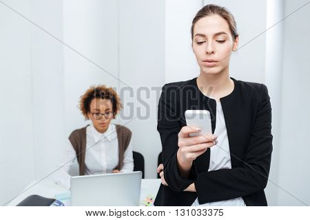 Two concentrated young businesswomen using smartphone and laptop in office
