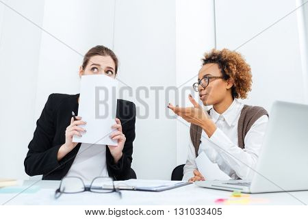 Serious strict african american businesswoman director sitting and talking with her scared young employee in office