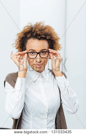 Portrait of attractive african american young businesswoman in glasses standing in office