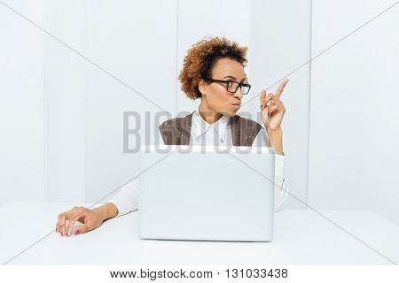 Pretty inspired african american curly businesswoman pointing up and having an idea sitting on workplace with laptop