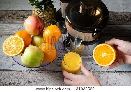 Man Preparing Fresh Orange Juice. Fruits In Background