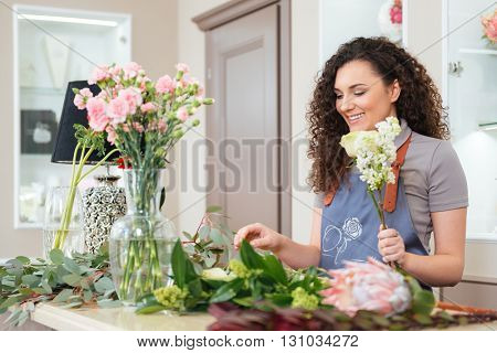 Smiling pretty young woman florist standing and making bouquet in flower shop