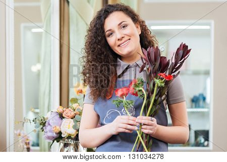 Portrait of beautiful curly woman florist standing in flower shop