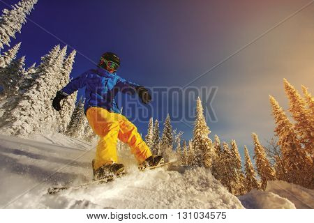 Jumping snowboarder on snowboard in mountains in ski resort on blue sky background