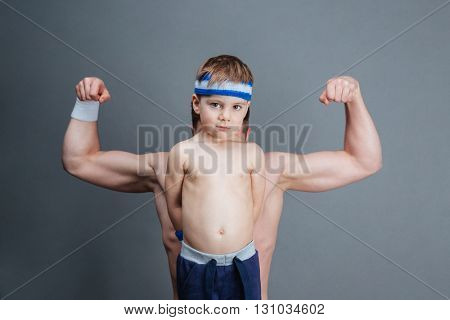 Father hiding behind his little son and showing biceps over grey background