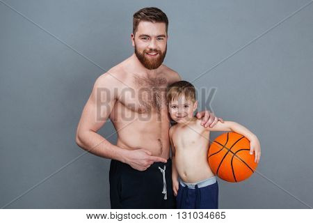 Potrait of happy shirtless dad and son standing and holding basketball ball over grey background