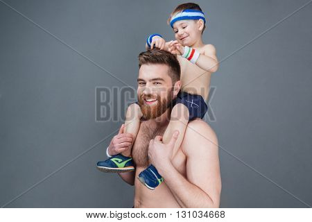 Cute smiling little boy sitting on his father shoulders over grey background
