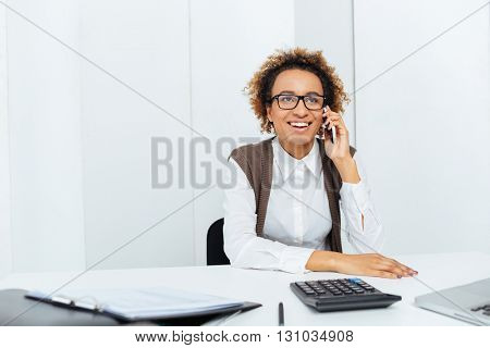 Happy african american young woman accountant sitting and talking on cell phone in office