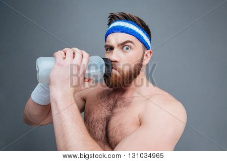 Suspicious shirtless young sportsman drinking water and looking at camera over grey background
