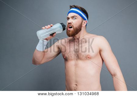 Bearded young sportsman standing and drinking water over grey background
