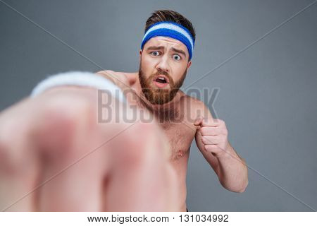 Scared confused bearded sportsman punching at camera over grey background