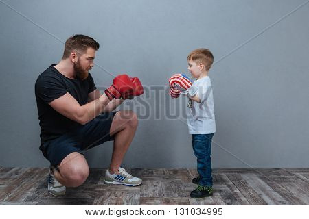 Dad and little son playing in boxing gloves together over grey background