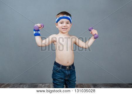 Happy cute little boy standing and doing exercises with dumbbells over grey background