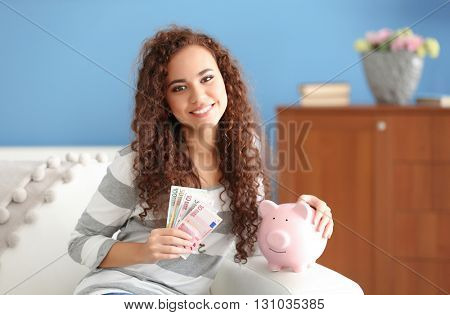 Beautiful young girl with cash and piggy bank on couch