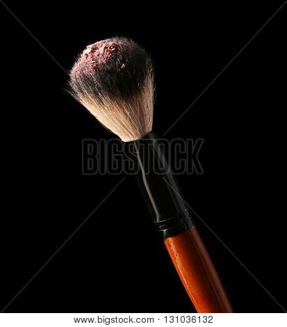 Make up brush with powder on black background