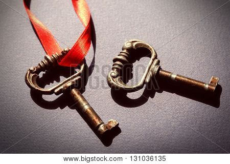 Vintage keys with a red ribbon on dark blue background