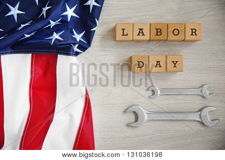 Construction tools, American flag and wooden cubes with text LABOR DAY on wooden background
