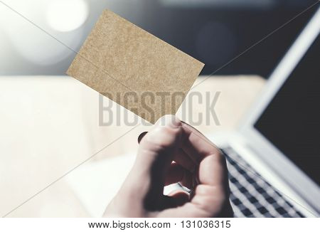 Closeup Image Man Showing Blank Craft Business Card and Using  Modern Laptop on Wood table Blurred Background. Mockup Ready for Private Information. Sunlight Flares. Horizontal mock up