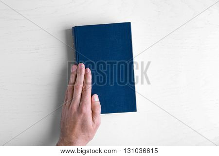 Male hand hold the blue book on white table.