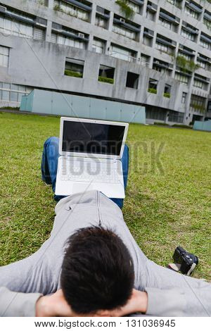 college student lying on a grass with laptop at campus