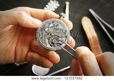Watchmaker hands repairing mechanism of old watch closeup
