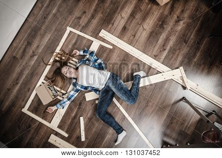 Happy Woman Having Fun Assembling Furniture.