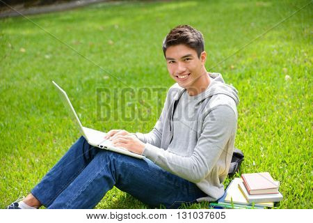 college student sitting use laptop in her hand at campus