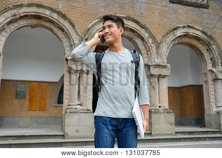 portrait of male college student doing use mobile phone at campus