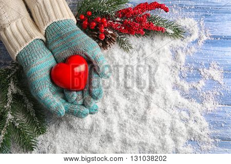 Female hands in mittens with decorative heart on snow background